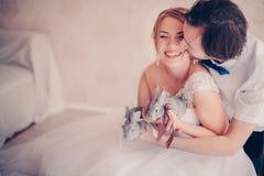 Nahaufnahmefoto der schönen lächelnden Braut mit den Kaninchen in ihren Händen geküsst vom Bräutigam in den warmen Farben Lizenzfreies Stockfoto