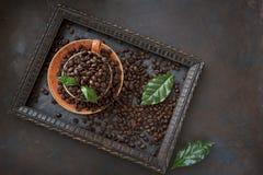 Nahaufnahmefoto der Schale mit AromaKaffeebohnen und frischen grünen Blättern im Rahmen auf schwarzem Tabellenhintergrund Lizenzfreie Stockfotos
