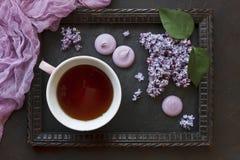 Nahaufnahmefoto der Teeschale mit Makronen und schöner frischer Flieder im Rahmen auf schwarzem Tabellenhintergrund Stockfotos