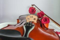 Nahaufnahmefoto der Violine und Rosen auf Anmerkung bedecken Stockfoto