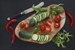 Nahaufnahmefoto des Frischgemüses auf hölzernem Schneidebrett mit Messer auf Schwarzem concreted Tabellenhintergrund Lizenzfreies Stockfoto