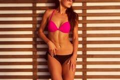 Nahaufnahmefoto des gebräunten Brunettemodells mit dem sexy Körper, der an im Bikini und in der Sonnenbrille gegen hölzernes Gitt Stockfoto