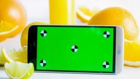 Nahaufnahmefoto des Handys mit grünem chromakey Schirm nahe bei frischen Früchten auf weißer Tabelle Vervollkommnen Sie für die E Stockfotografie