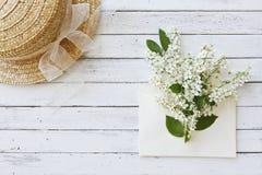 Nahaufnahmefoto des Hutes nahe Umschlag mit schönen blühenden Baumasten auf weißem hölzernem Hintergrund Lizenzfreies Stockbild
