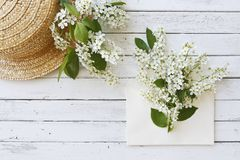 Nahaufnahmefoto des Hutes nahe Umschlag mit schönen blühenden Baumasten auf weißem hölzernem Hintergrund Stockbilder