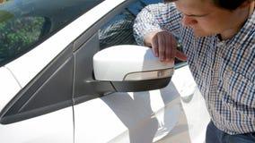 Nahaufnahmefoto des jungen männlichen Fahrers, der verkratzten Autoseitenspiegel betrachtet Lizenzfreie Stockbilder