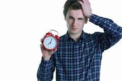 Nahaufnahmefoto des jungen Mannes des Umkippens mit der Hand im Haar, das roten Wecker, lokalisiert über weißem Hintergrund hält lizenzfreies stockbild