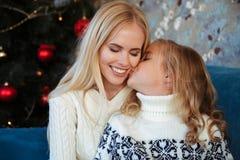 Nahaufnahmefoto des kleinen Mädchens in gestrickter Strickjacke küssen ihre Mutter stockbilder