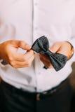 Nahaufnahmefoto des Mannes im Smoking, der sein bowtie, zwei Hände, keine Jacke hält stockbild