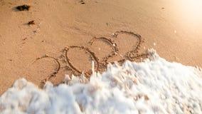 Nahaufnahmefoto des Meereswogen über 2022 Zahlen des neuen Jahres rollend geschrieben auf nass Sand am Inselstrand Konzept des ne stockfoto