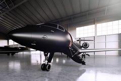 Nahaufnahmefoto des schwarzen Matte Luxury Generic Design Private-Jet-Parkens im Hangarflughafen Konkreter Boden Geschäft Stockbild