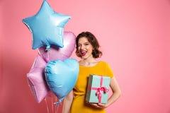 Nahaufnahmefoto des spielerischen Geburtstagsmädchens mit den roten Lippen blinzelt ein Lizenzfreies Stockfoto