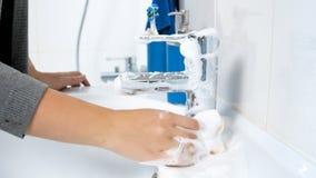 Nahaufnahmefoto des weiblichen Händewaschenwannen-Wasserhahns mit Reinigungsmittel lizenzfreie stockfotografie