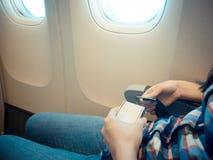 Nahaufnahmefoto des weiblichen Reisenden das Flugzeug nehmend Stockbild