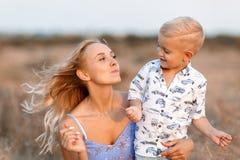 Nahaufnahmefoto einer reizenden Frau, die mit ihrem netten Sohn auf einem unscharfen Naturhintergrund spielt draußen Kopieren Sie lizenzfreie stockbilder