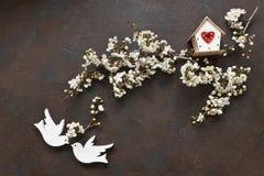 Nahaufnahmefoto schönen weißen blühenden Cherry Tree-branche mit zwei hölzernen Vögeln und Vogelhaus S Lizenzfreies Stockbild