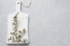 Nahaufnahmefoto von blühenden Blumen des schönen Weiß der Kirschbaumniederlassung auf weißem hölzernem Schneidebrett auf grauem H Lizenzfreies Stockfoto