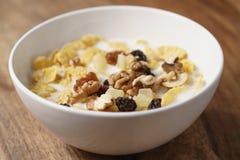 Nahaufnahmefoto von Corn Flakes mit Früchten und Nüssen in der weißen Schüssel auf hölzerner Tabelle Lizenzfreie Stockfotos