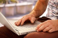 Nahaufnahmefoto von den männlichen Händen, die auf Laptop schreiben Stockfotografie
