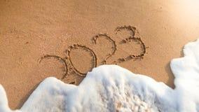 Nahaufnahmefoto von den Meereswogen, die über 2023 Zahlen geschrieben auf nass Sand rollen Konzept des neuen Jahres, des Weihnach lizenzfreie stockfotografie