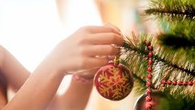 Nahaufnahmefoto von den weiblichen Händen, die Weihnachtsbaum am Morgen verzieren lizenzfreie stockfotografie