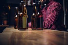 Nahaufnahmefoto von Flaschen Handwerksbier auf hölzernem Barzähler an der indie Brauerei lizenzfreies stockfoto