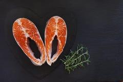 Nahaufnahmefoto von frischen Lachsfischen mit Seesalz- und -kalkscheiben auf schwarzem Tabellenhintergrund Stockbilder