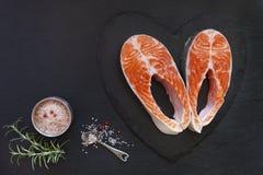 Nahaufnahmefoto von frischen Lachsfischen mit Seesalz- und -kalkscheiben auf schwarzem Tabellenhintergrund Stockfotos