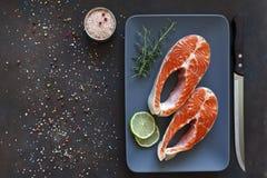Nahaufnahmefoto von frischen Lachsfischen mit Seesalz- und -kalkscheiben auf schwarzem Tabellenhintergrund Stockfoto