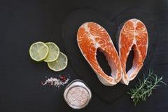 Nahaufnahmefoto von frischen Lachsfischen mit Seesalz- und -kalkscheiben auf schwarzem Tabellenhintergrund Lizenzfreie Stockfotografie