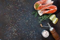 Nahaufnahmefoto von frischen Lachsfischen mit Seesalz- und -kalkscheiben auf schwarzem Tabellenhintergrund Beschneidungspfad eing Stockbild