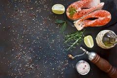 Nahaufnahmefoto von frischen Lachsfischen mit Seesalz- und -kalkscheiben auf schwarzem Tabellenhintergrund Beschneidungspfad eing Stockfotos