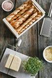 Nahaufnahmefoto von geschmackvollen gebackenen Stöcken mit Käse im Kasten mit Grünpflanze auf Holztischhintergrund Lizenzfreies Stockbild