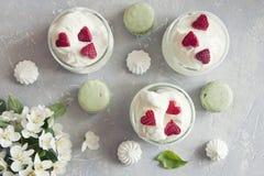 Nahaufnahmefoto von kalten Schalen Eiscreme mit grünen Makronen und schönen frischen Blumen auf grauem Tabellenhintergrund Lizenzfreies Stockfoto