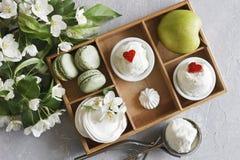 Nahaufnahmefoto von kalten Schalen Eiscreme mit Makronen, grünem Apfel in der Holzkiste und schönen frischen Blumen auf grauem Ta Lizenzfreie Stockbilder