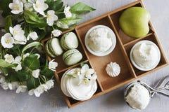 Nahaufnahmefoto von Makronen, von grünem Apfel und von schönen frischen Blumen auf grauem Tabellenhintergrund Stockbilder