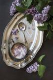 Nahaufnahmefoto von schönen frischen lila Blumen im Zucker auf Metallweinlesebehälter auf schwarzem Tabellenhintergrund Lizenzfreies Stockbild