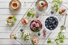 Nahaufnahmefoto von selbst gemachten Kuchen mit mascarpone Käse, Zimt, Erdbeeren, Blaubeeren und schönem wildem Apfelbaum floweri Stockfotografie