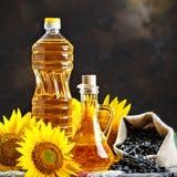 Nahaufnahmefoto von Sonnenblumen und von Sonnenblumenöl mit Samen an auf einem Holztisch Bio- und organisches Konzept des Produkt Stockbild