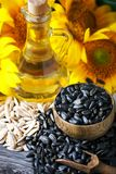 Nahaufnahmefoto von Sonnenblumen und von Sonnenblumenöl mit Samen an auf einem Holztisch Bio- und organisches Konzept des Produkt Lizenzfreie Stockfotografie