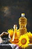Nahaufnahmefoto von Sonnenblumen und von Sonnenblumenöl mit Samen an auf einem Holztisch Bio- und organisches Konzept des Produkt Lizenzfreie Stockfotos