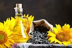 Nahaufnahmefoto von Sonnenblumen und von Sonnenblumenöl mit Samen an auf einem Holztisch Bio- und organisches Konzept des Produkt Stockfotografie