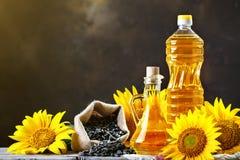 Nahaufnahmefoto von Sonnenblumen und von Sonnenblumenöl mit Samen an auf einem Holztisch Bio- und organisches Konzept des Produkt Lizenzfreies Stockbild
