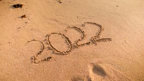 Nahaufnahmefoto von 2022 Zahlen geschrieben auf nass Sand auf dem Ozeanstrand Konzept des neuen Jahres, des Weihnachten und der R lizenzfreie stockbilder