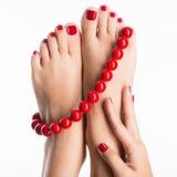 Nahaufnahmefoto weiblichen Füße mit schöner roter Pediküre Stockbilder