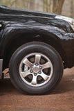 Nahaufnahmefotorad von SUV, das im Wald steht Lizenzfreie Stockfotos