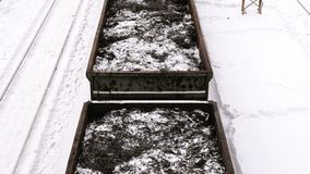 Nahaufnahmefracht vagons mit Metallschnitzeln unter Schienen am Bahnhof im Winter stock footage