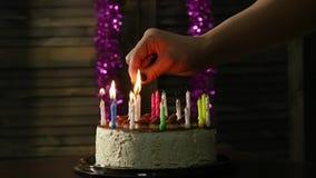 Nahaufnahmefrau beleuchtet Kerzen auf geschmackvollem Geburtstagskuchen Langsame Bewegung stock video footage