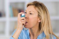Nahaufnahmefrau, die Asthmainhalator im Wohnzimmer verwendet stockbild