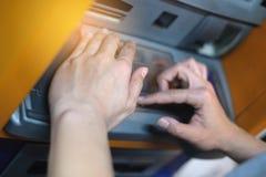 Nahaufnahmefrau, die ATM-Maschinentastatur mit ihren Händen bedeckt und Zahltaste an der ATM-Maschine, Handpressegeld von ATM drü stockfoto